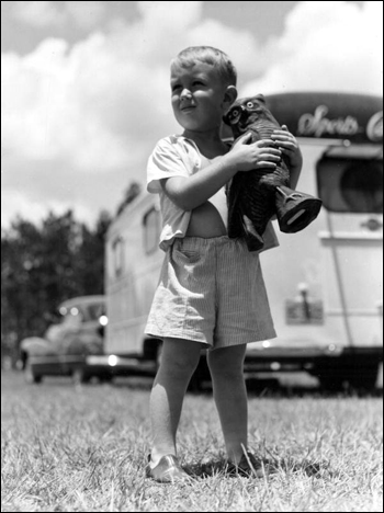 Michael Sadler holding a sculpture stands outside a trailer: Dead Lakes, Florida (1947)