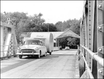 Car and trailer crossing a bridge: Astor, Florida (1957)