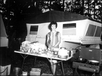 Young woman prepares a meal at a camping convention: Gainesville, Florida (1962)