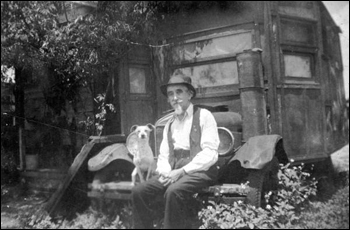 Retired railroad man sitting on the bumper of his house-car (1931)