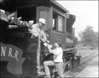 Young visitor gets autograph from train engineer at Pioneer City: Davie, Florida (1967)