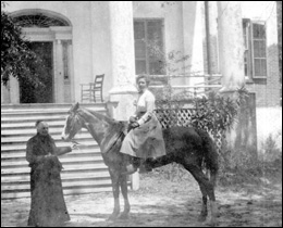 "Ellen Call Long leads a horse ridden by a lady in front of ""The Grove"": Tallahassee, Florida"
