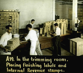 In the trimming room, placing finishing labels and Internal Revenue stamps (192-)