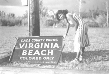 Woman by sign blown down during hurricane: Virginia Beach, Florida (1950)