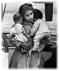 Young Cuban refugee holding her dolls in airport (1961)