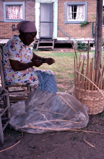 Lucreaty Clark preparing a strip of white oak for her basket (not after 1979)