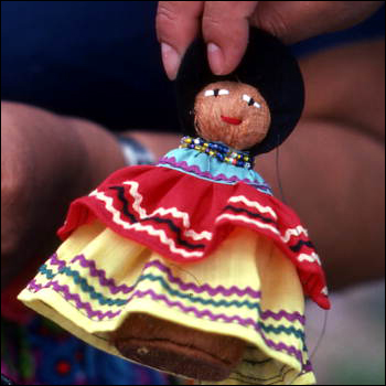 Seminole doll made by Mary Billie being held up for the camera: Big Cypress Seminole Indian Reservation, Florida