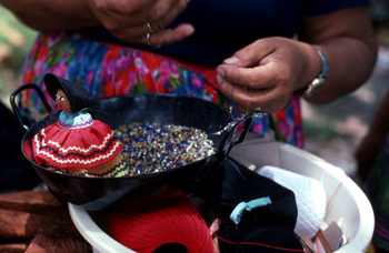 Mary B. Billie making a necklace for her Seminole doll: Big Cypress Seminole Indian Reservation, Florida (not after 1980)