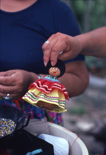 Seminole doll made by Mary Billie being held up for the camera: Big Cypress Seminole Indian Reservation, Florida (not after 1980)