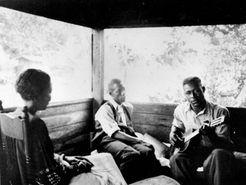 Gabriel Brown playing guitar as Rochelle French and Zora Neale Hurston listen: Eatonville, Florida (1935)