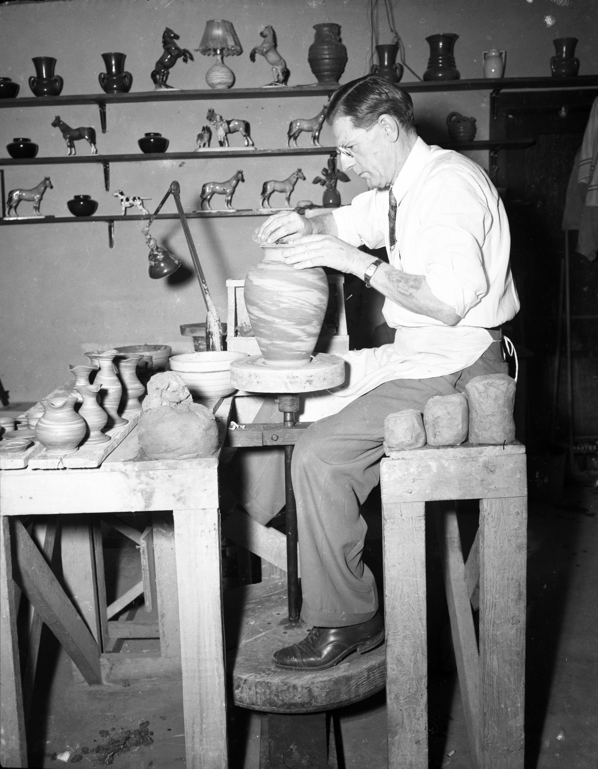Henry Graack at the wheel in his shop making pottery for tourists at Silver Springs.