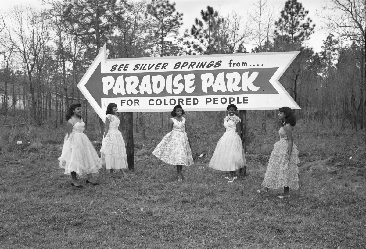 Young women posing by Paradise Park billboard.