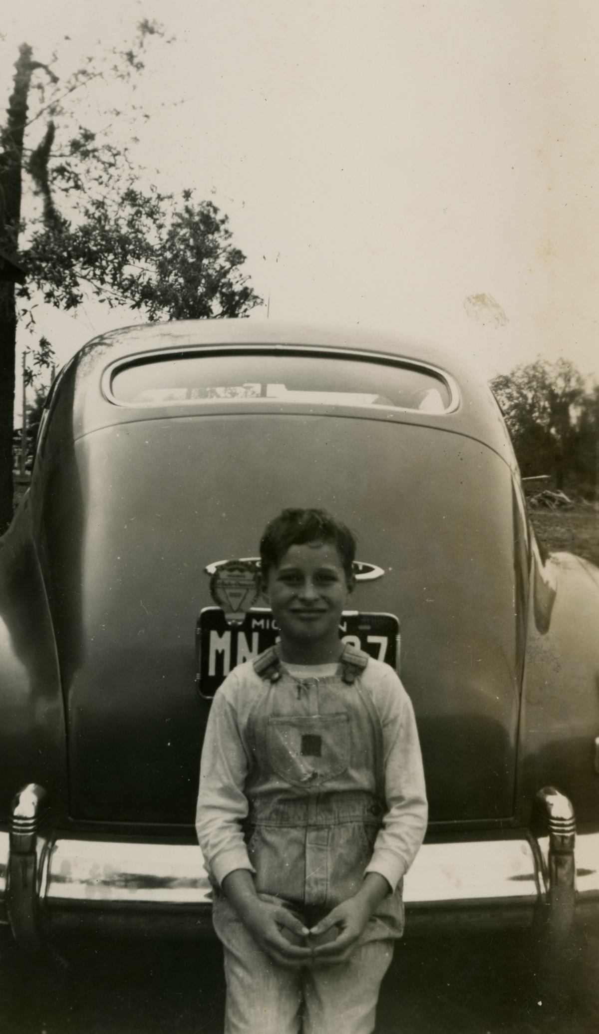 Hall family member from Michigan posing on the car bumper during Central Florida vacation.