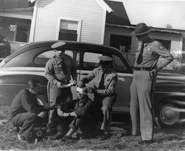 Florida Highway Patrol Lt. J.W. Hagan and Capt. Martin administering first aid - Panama City, Florida.