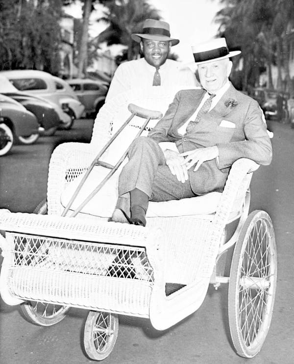 Colonel Edward R. Bradley in a bicycle cart pushed by an African American man.