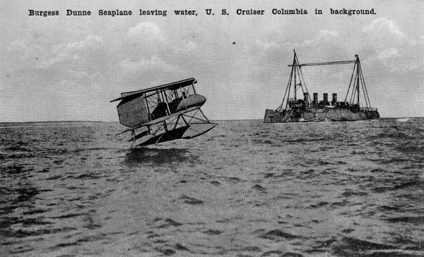 Burgess Dunne seaplane leaving water, U.S. Cruiser Columbia in background..