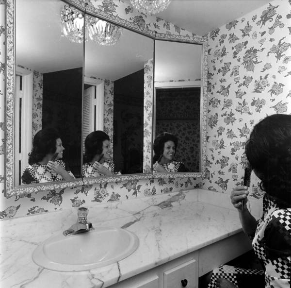 Unidentified woman fixing her hair in front of a mirror - Fort Lauderdale, Florida.