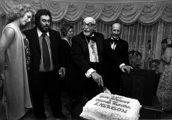 Luciano Pavarotti, at left, watching as Fort Lauderdale Symphony music director Emerson Buckley cuts his birthday cake.
