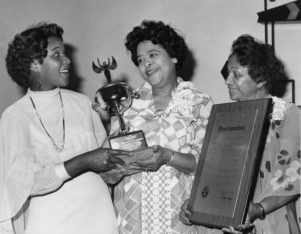 Marsha Dean (later Phelts) presenting an award to Mary Littlejohn Singleton as Bernice Cornell Dawes looks on.