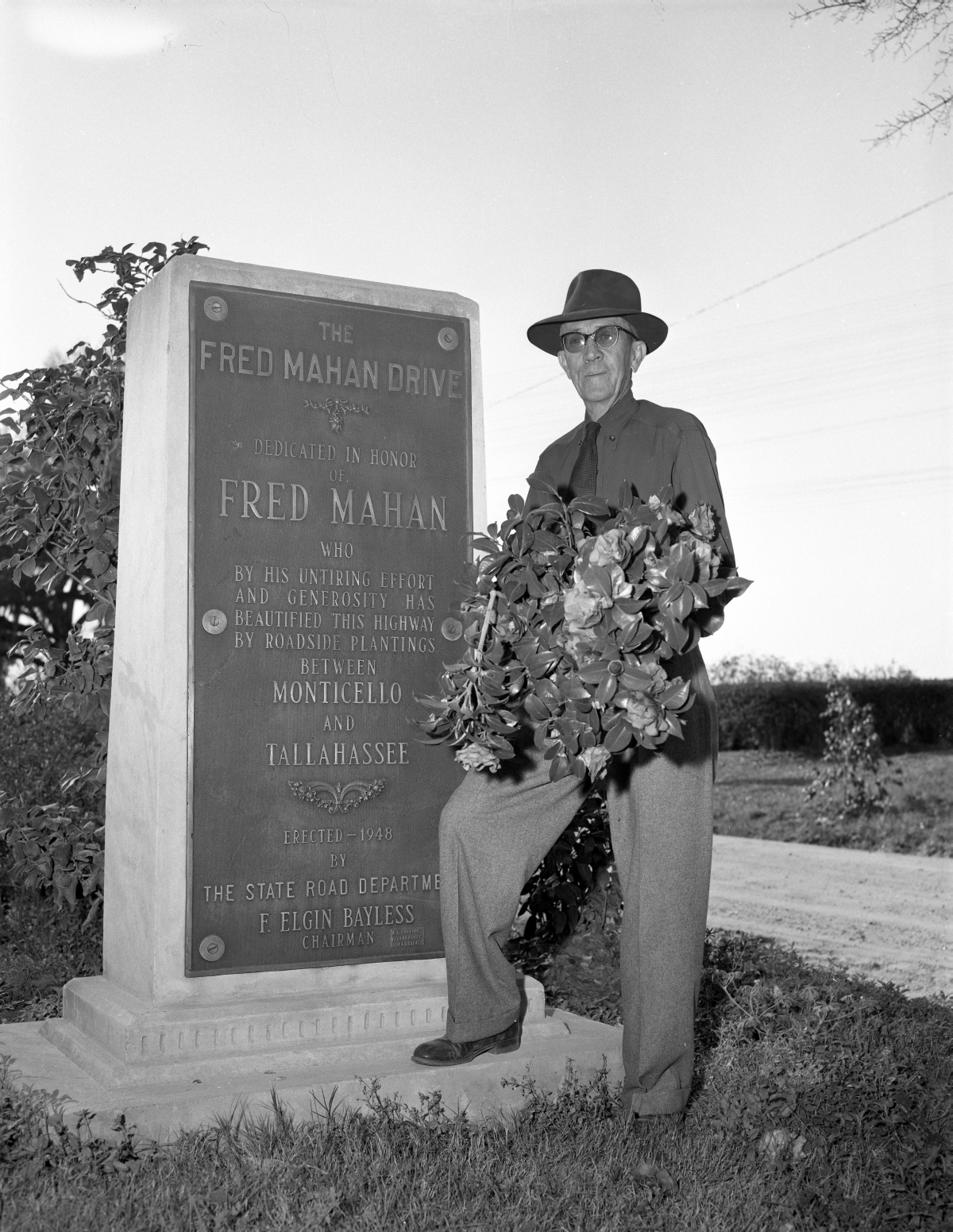 Fred Mahan standing beside the Fred Mahan Drive marker.
