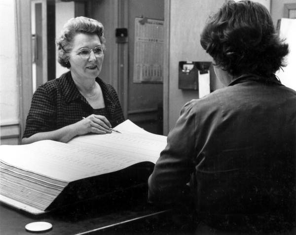 Employee at the Office of County Tax Assessor helping patron in the county courthouse - Tallahassee, Florida.
