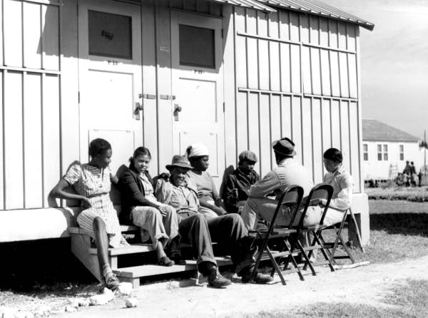 Migrant workers relaxing outside labor camp shelters - Belle Glade, Florida.