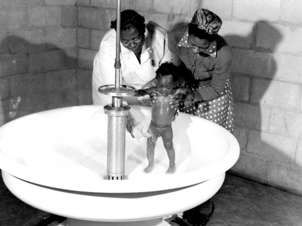 African American baby being given a bath at a migrant labor camp - Belle Glade, Florida.