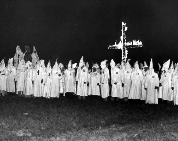 Ku Klux Klan members gathered in front of a burning cross - Tallahassee, Florida.