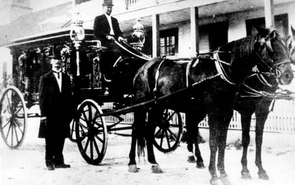 Undertaker Benjamin Lopez standing beside his funeral carriage - Key West, Florida.