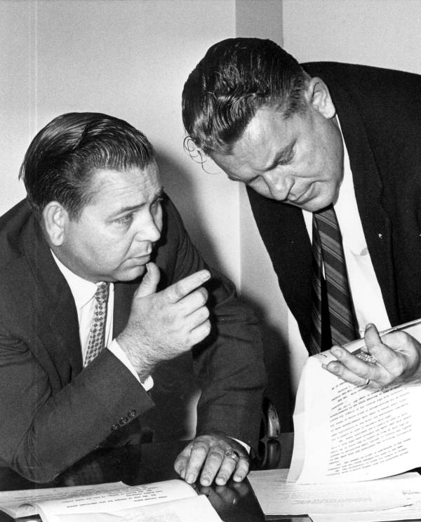 """Representatives James N. """"Gator"""" Beck (left) and Ralph Erickson discussing a new bill for motel room price - Tallahassee, Florida."""