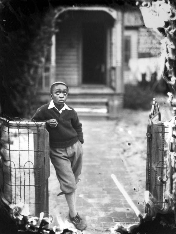 African American boy leaning on a fence.