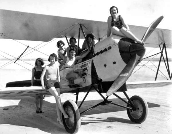 Young women climbing on an airplane parked on the beach.