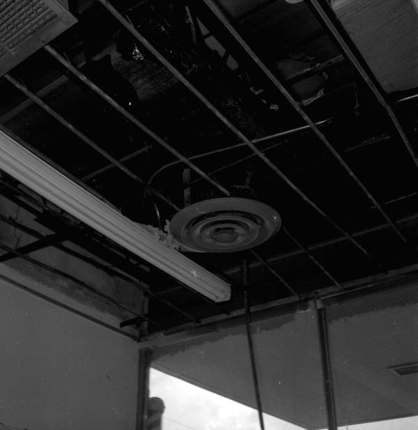 Interior view showing ceiling damaged by fire at a barbershop in Tallahassee, Florida.