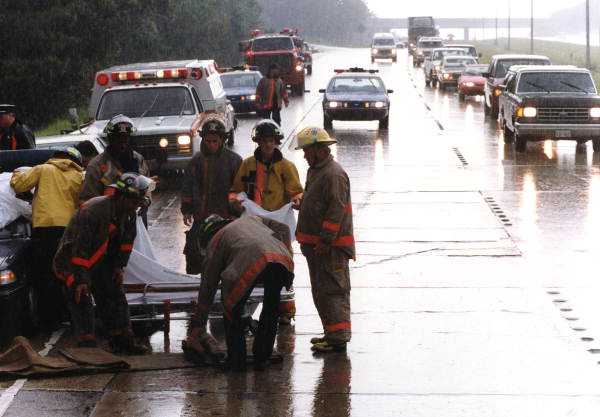 View showing TFD firefighters standing around gurney on I-10 in Tallahassee, Florida.